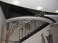 изогнутый черный натяжной потолок в холле с лестницей